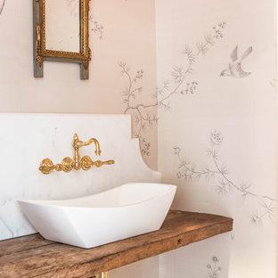 На фото: туалет среднего размера в современном стиле с настольной раковиной, столешницей из дерева, бежевыми стенами, темным паркетным полом и коричневой столешницей с
