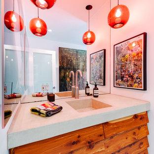 На фото: туалет среднего размера в стиле фьюжн с монолитной раковиной, фасадами с филенкой типа жалюзи, фасадами цвета дерева среднего тона, бетонным полом и столешницей из известняка с