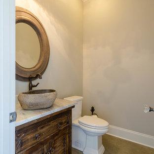 На фото: туалет среднего размера в классическом стиле с фасадами с филенкой типа жалюзи, темными деревянными фасадами, серыми стенами, бетонным полом и столешницей из гранита с