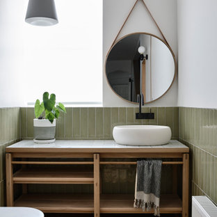 Cette photo montre un WC et toilettes tendance de taille moyenne avec un placard en trompe-l'oeil, des portes de placard en bois clair, un WC suspendu, un carrelage vert, des carreaux de céramique, un mur blanc, un sol en bois clair, une vasque, un plan de toilette en carrelage, un sol marron et un plan de toilette blanc.