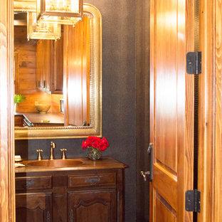 Modelo de aseo tradicional, de tamaño medio, con armarios con paneles con relieve, puertas de armario de madera en tonos medios, sanitario de una pieza, paredes grises, suelo de ladrillo, lavabo integrado y encimera de cobre