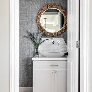 Exemple d'un petit WC et toilettes bord de mer avec des portes de placard grises, un sol en bois clair, une vasque, un placard à porte shaker, un mur gris, un sol beige et un plan de toilette blanc.