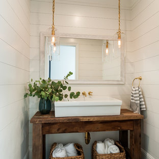 Inspiration for a small cottage white tile limestone floor powder room remodel in Los Angeles with open cabinets, medium tone wood cabinets, white walls, a vessel sink, wood countertops and brown countertops