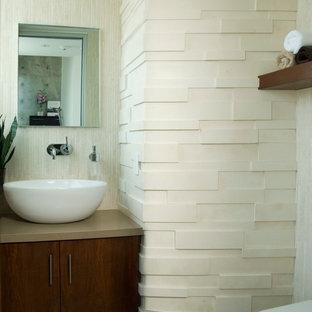 На фото: туалет среднего размера в стиле модернизм с фасадами с утопленной филенкой, темными деревянными фасадами, бежевой плиткой, плиткой из травертина, бежевыми стенами, настольной раковиной и столешницей из искусственного кварца