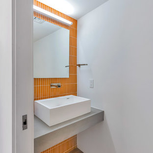 This is an example of a contemporary cloakroom in Phoenix with orange tiles, white walls, medium hardwood flooring, a vessel sink, brown floors and grey worktops.