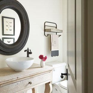 Réalisation d'un petit WC et toilettes champêtre avec un placard en trompe-l'oeil, des portes de placard en bois clair, un mur blanc, un sol en bois brun, une vasque, un plan de toilette en bois, un WC séparé et un plan de toilette beige.