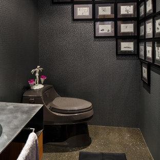 Imagen de aseo de estilo zen, de tamaño medio, con encimera de acero inoxidable, paredes negras, suelo de cemento, sanitario de dos piezas y baldosas y/o azulejos grises