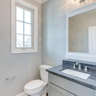 Idee per un bagno di servizio american style con ante con riquadro incassato, ante grigie, WC a due pezzi, pareti grigie, parquet scuro, lavabo da incasso, top in granito, pavimento marrone e top grigio