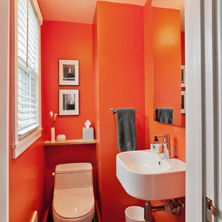 This is an example of a small modern cloakroom in New York with a wall-mounted sink, a one-piece toilet, black tiles, orange walls and ceramic flooring.