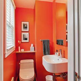 ニューヨークの小さいモダンスタイルのおしゃれなトイレ・洗面所 (壁付け型シンク、一体型トイレ、黒いタイル、オレンジの壁、セラミックタイルの床) の写真