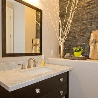 Idées déco pour un petit WC et toilettes classique avec un placard en trompe-l'oeil, des portes de placard en bois sombre, un carrelage gris, un carrelage de pierre, un mur blanc, un lavabo encastré, un plan de toilette en marbre et un plan de toilette blanc.