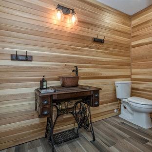 バンクーバーの中サイズのラスティックスタイルのおしゃれなトイレ・洗面所 (オープンシェルフ、黒いキャビネット、分離型トイレ、ベージュの壁、磁器タイルの床、ベッセル式洗面器、木製洗面台、茶色い床) の写真