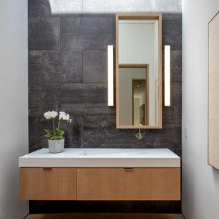 Inspiration för moderna vitt toaletter, med släta luckor, skåp i ljust trä, svart kakel, vita väggar, ljust trägolv, ett integrerad handfat och beiget golv