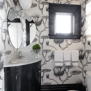 Пример оригинального дизайна: большой туалет в стиле фьюжн с фасадами с утопленной филенкой, черными фасадами, раздельным унитазом, врезной раковиной, мраморной столешницей и белой столешницей