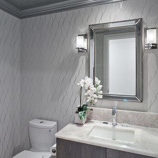 Réalisation d'un WC et toilettes design de taille moyenne avec un placard à porte shaker, des portes de placard marrons, un WC à poser, un mur blanc, un lavabo encastré et un plan de toilette beige.