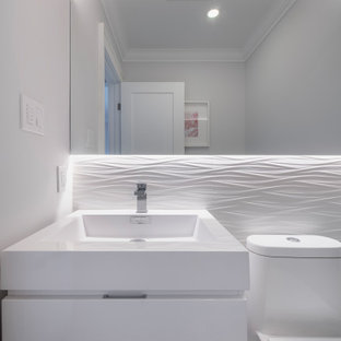 Photo of a medium sized modern cloakroom in Toronto with flat-panel cabinets, white cabinets, a one-piece toilet, white tiles, ceramic tiles, grey walls, slate flooring, an integrated sink, engineered stone worktops, grey floors and white worktops.