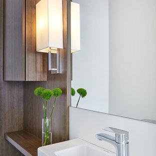 Пример оригинального дизайна: маленький туалет в стиле модернизм с плоскими фасадами, фасадами цвета дерева среднего тона, раздельным унитазом, белой плиткой, керамогранитной плиткой, белыми стенами, полом из керамогранита, столешницей из дерева, коричневой столешницей, подвесной раковиной и коричневым полом