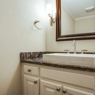 Cette image montre un petit WC et toilettes traditionnel avec une vasque, des portes de placard blanches, un plan de toilette en granite, un mur beige et un placard avec porte à panneau surélevé.