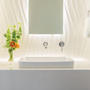 Стильный дизайн: туалет среднего размера в стиле модернизм с белой плиткой, белыми стенами, накладной раковиной и столешницей из искусственного кварца - последний тренд