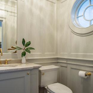 Cette photo montre un petit WC et toilettes chic avec un WC séparé, un mur gris, un lavabo encastré, un plan de toilette en quartz, un placard à porte affleurante, des portes de placard grises et un plan de toilette beige.