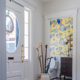На фото: туалет среднего размера в классическом стиле с фасадами островного типа, темными деревянными фасадами, унитазом-моноблоком, желтой плиткой, желтыми стенами, темным паркетным полом, накладной раковиной, мраморной столешницей, коричневым полом и белой столешницей с