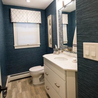 Cette photo montre un petit WC et toilettes chic avec un placard à porte plane, des portes de placard blanches, un WC à poser, un carrelage bleu, des plaques de verre, un mur bleu, un sol en carrelage de céramique, un lavabo encastré et un sol beige.