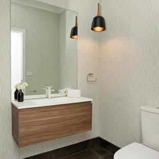 Cette photo montre un petit WC et toilettes tendance avec un placard à porte plane, des portes de placard en bois brun, un WC à poser, des carreaux de miroir, un mur gris, un sol en carrelage de céramique, un lavabo suspendu, un plan de toilette en quartz modifié et un sol noir.
