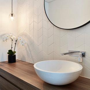 На фото: туалет в современном стиле с плоскими фасадами, фасадами цвета дерева среднего тона, унитазом-моноблоком, белой плиткой, керамогранитной плиткой, белыми стенами, темным паркетным полом, настольной раковиной, столешницей из дерева, коричневым полом и коричневой столешницей с