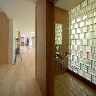 Diseño de aseo madera, contemporáneo, pequeño, madera, con sanitario de pared, suelo de madera clara, lavabo suspendido, encimera de acero inoxidable y madera