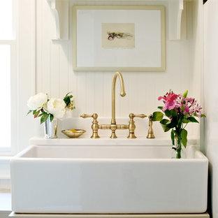 Exemple d'un petit WC et toilettes chic avec un placard à porte affleurante, des portes de placard grises et un mur blanc.