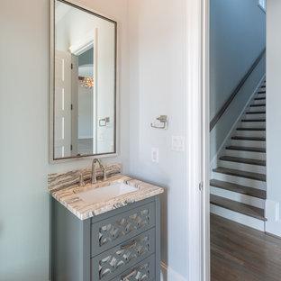 На фото: маленький туалет в стиле современная классика с фасадами островного типа, синими фасадами, серыми стенами, полом из керамогранита, врезной раковиной, столешницей из известняка, серым полом и серой столешницей с
