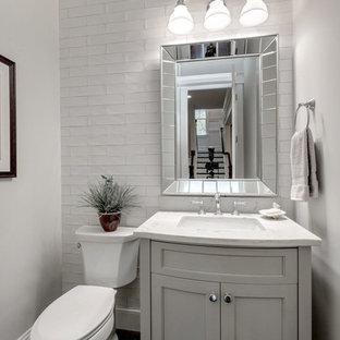Idées déco pour un WC et toilettes campagne de taille moyenne avec un placard avec porte à panneau encastré, des portes de placard grises, un WC séparé, un carrelage blanc, un carrelage métro, un mur gris, un lavabo encastré, un plan de toilette en quartz et un plan de toilette blanc.