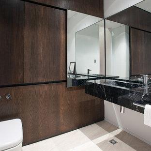 На фото: туалеты в современном стиле с монолитной раковиной, плоскими фасадами, темными деревянными фасадами, мраморной столешницей и полом из травертина