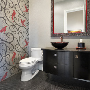 Design ideas for a contemporary cloakroom in Edmonton with freestanding cabinets, black cabinets, a one-piece toilet, multi-coloured tiles, mosaic tiles, multi-coloured walls, a vessel sink and black floors.