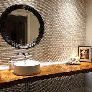 Пример оригинального дизайна: маленький туалет в современном стиле с настольной раковиной, столешницей из дерева, белой плиткой, белыми стенами, плиткой мозаикой и коричневой столешницей