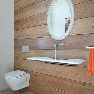 Пример оригинального дизайна: туалет в современном стиле с подвесной раковиной, инсталляцией и полом из галечной плитки