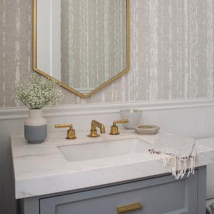 Cette photo montre un petit WC et toilettes chic avec des portes de placard grises, un WC séparé, un mur beige, un lavabo encastré, un plan de toilette en marbre, un placard avec porte à panneau encastré et un plan de toilette blanc.