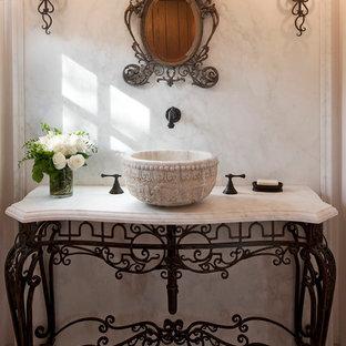 Diseño de aseo mediterráneo con lavabo sobreencimera y baldosas y/o azulejos de mármol