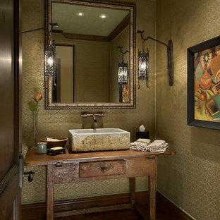 Ejemplo de aseo mediterráneo, pequeño, con encimera de madera, lavabo sobreencimera, armarios abiertos, puertas de armario de madera oscura, paredes amarillas, suelo de madera oscura y encimeras marrones