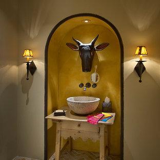 Inspiration pour un petit WC et toilettes méditerranéen avec un plan de toilette en bois, une vasque, un mur beige, un sol en brique, des portes de placard en bois clair et un plan de toilette beige.