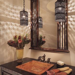 Пример оригинального дизайна: туалет в средиземноморском стиле с накладной раковиной, темными деревянными фасадами, столешницей из дерева и коричневой столешницей
