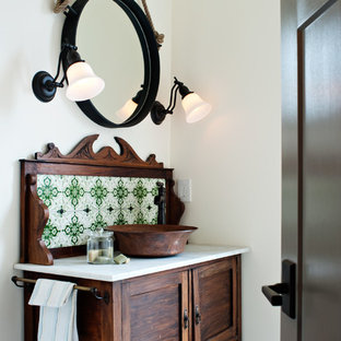 Inspiration for a mediterranean cloakroom in Vancouver with a vessel sink, freestanding cabinets, dark wood cabinets and green tiles.