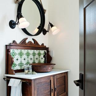 Ejemplo de aseo mediterráneo con lavabo sobreencimera, armarios tipo mueble, puertas de armario de madera en tonos medios y baldosas y/o azulejos verdes