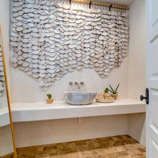 Ejemplo de aseo mediterráneo con paredes blancas, lavabo sobreencimera, suelo marrón y encimeras blancas