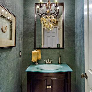 Modelo de aseo mediterráneo, pequeño, con armarios tipo mueble, puertas de armario de madera en tonos medios, paredes grises, lavabo integrado y encimera de vidrio