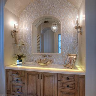 На фото: огромный туалет в средиземноморском стиле с фасадами островного типа, фасадами цвета дерева среднего тона, унитазом-моноблоком, бежевой плиткой, плиткой мозаикой, белыми стенами, настольной раковиной, столешницей из оникса, полом из керамогранита и белым полом с