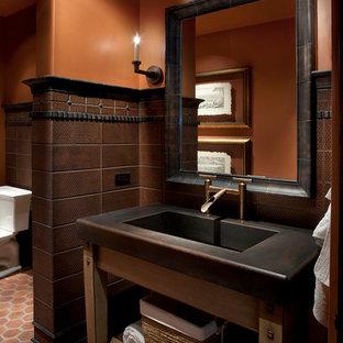 Idee per un piccolo bagno di servizio mediterraneo con lavabo integrato, piastrelle marroni, pareti arancioni, pavimento in terracotta e top nero