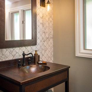 Cette photo montre un petit WC et toilettes méditerranéen avec un placard sans porte, des portes de placard marrons, un WC à poser, un carrelage noir et blanc, des carreaux de porcelaine, un mur beige, un sol en carrelage de porcelaine, un lavabo intégré, un plan de toilette en cuivre et un sol marron.
