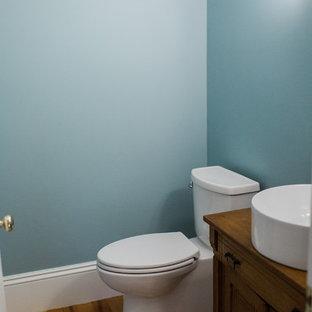 Idéer för att renovera ett litet vintage toalett, med luckor med upphöjd panel, skåp i mörkt trä, en toalettstol med separat cisternkåpa, blå väggar, ljust trägolv, ett fristående handfat, bänkskiva i travertin och brunt golv