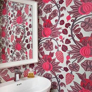 Cette image montre un WC et toilettes traditionnel avec un mur rose et un lavabo suspendu.
